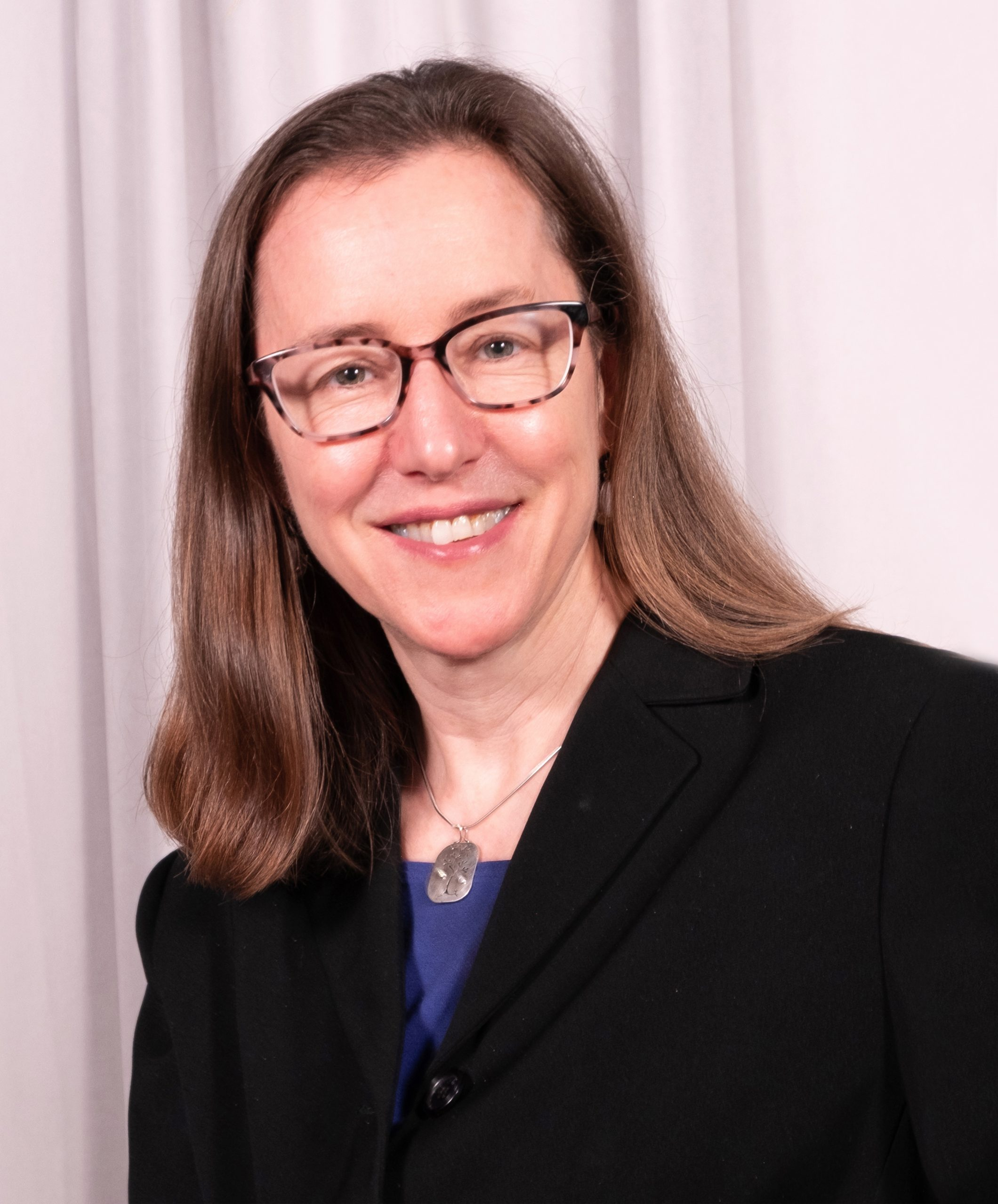 photos of HCAI Director Elizabeth Landsberg in front of white background. She is wearing a dark-colored jacket and glasses.
