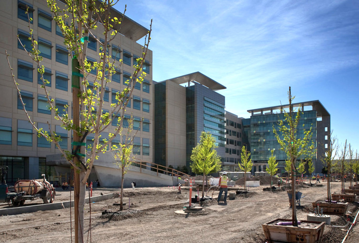 Photo of a hospital building under construction with landscaping being installed